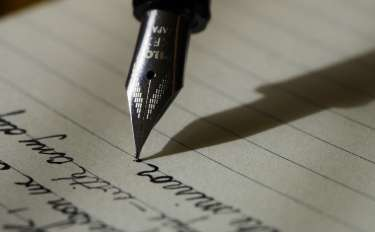 close image of the nib of a pen, writing elegantly on lined paper