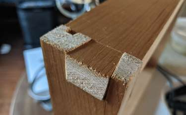A closeup of two pieces of wood joining at a dovetail join. The trapezoidal tail is on the top piece.