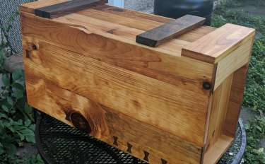 A wooden toolbox with inset sides, butterfly keys in the front, and wallnut bolsters holding up the inset lid.