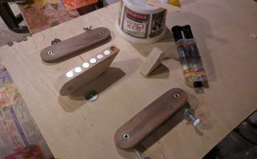 Several wood parts laid out on cardboard, with a tube of epoxy glue nearby.