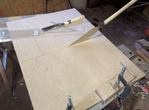 The pull saw in action, cutting down the middle of a piece of plywood