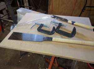 A pair of inexpensive pull saws on a piece of plywood