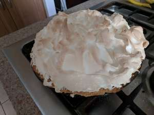 A photo of a lime meringue pie, cooling on a stovetop. The top is swirled and lightly browned.
