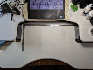 A top down shot of the desk space. An L ruler in metric measure shows the availble area for the keyboard and mouse.