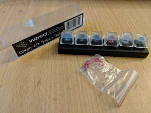 A key switch tester with the packaging in the background, and a packet of O-rings in the foreground