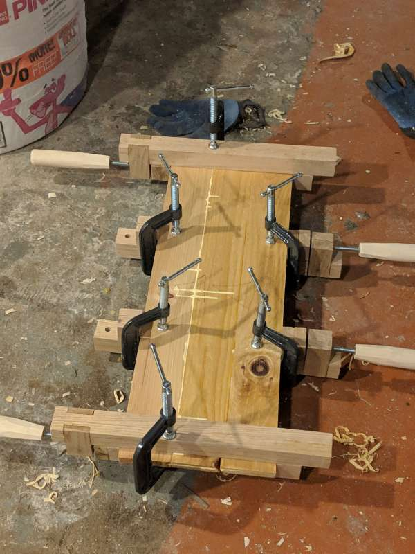 A panel being glued together with DIY bar clamps
