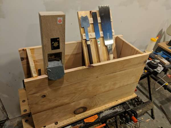 The shortened, glued together toolbox. A Japanese wood plane (kanna) rests on the front edge of the box, while the lid with saws rests against the back.
