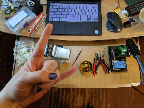 "A top-down shot of a desk with soldering equipment and parts. In the foreground a hand is making the ""horns"" gesture"