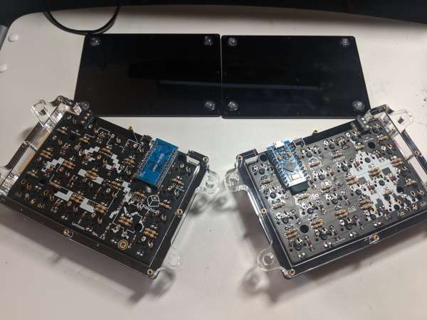 The back of the keyboard with the cover removed. The underlying PCB is visible, with one microcontroller on each side.