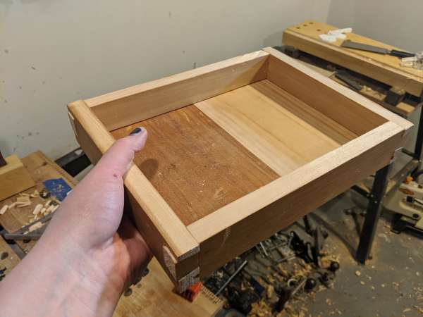 A completed tray with a bottom. The bottom is made of two pieces, one darker than the other.