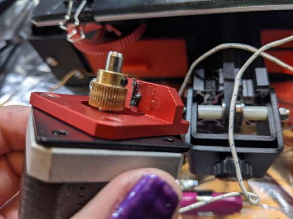 A partially disassembled extruder, showing melted filament around the exit port