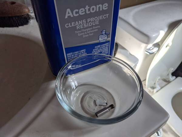 Hotend parts are cleaned in a glass bowl of acetone